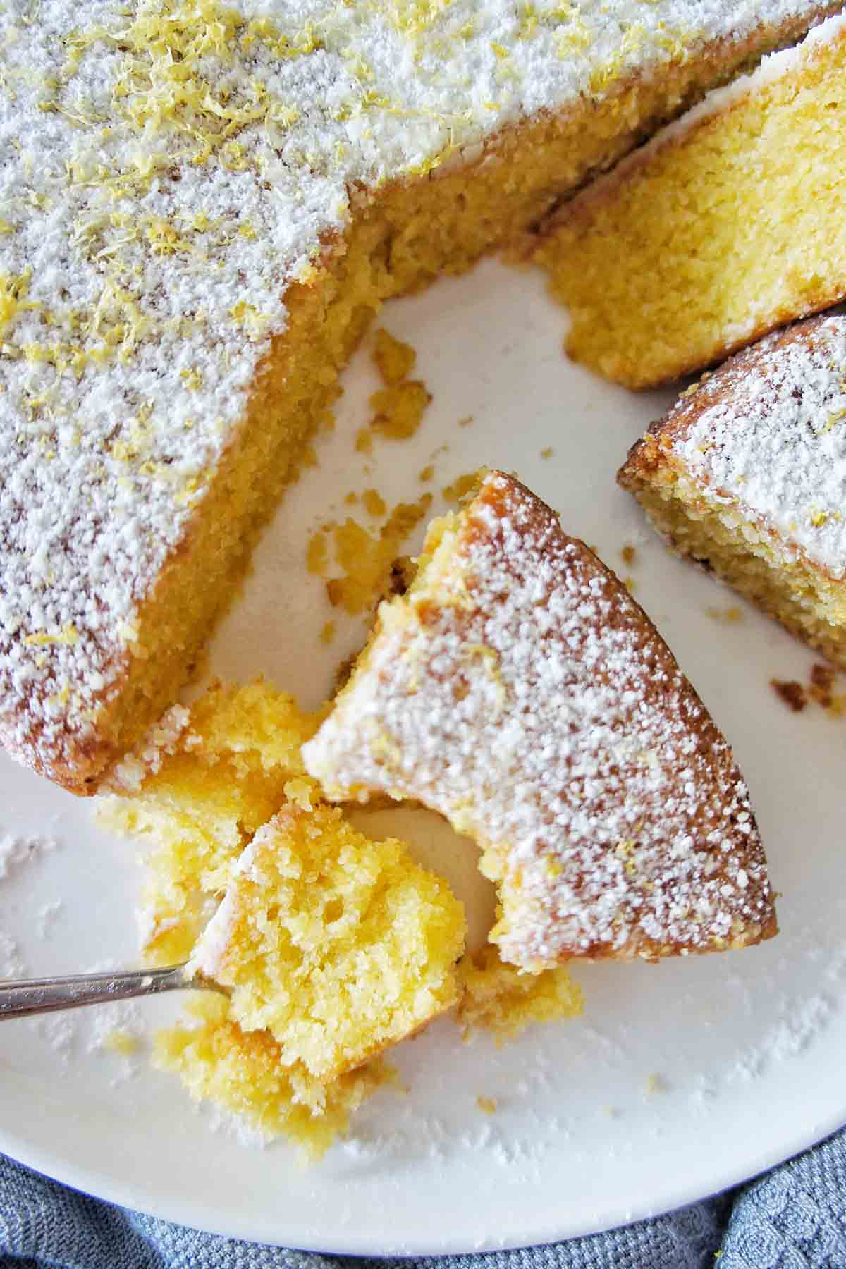 Teaspoon digging into slice of lemon polenta cake on a white plate