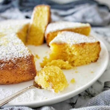 Lemon Polenta Cake slices on a white plate with silver spoon full of yellow fluffy cake
