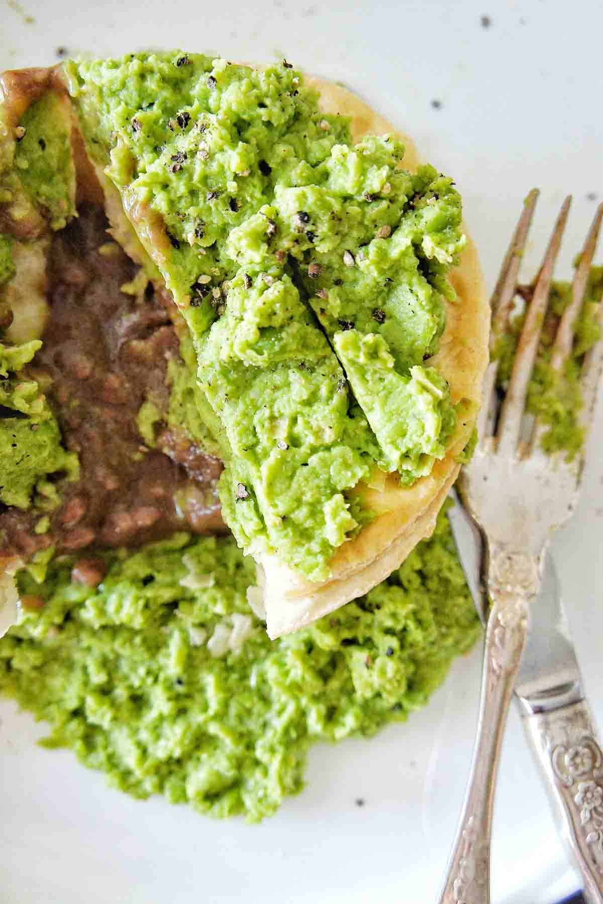 Mashed peas on top of a cut open meat pie on a white plate