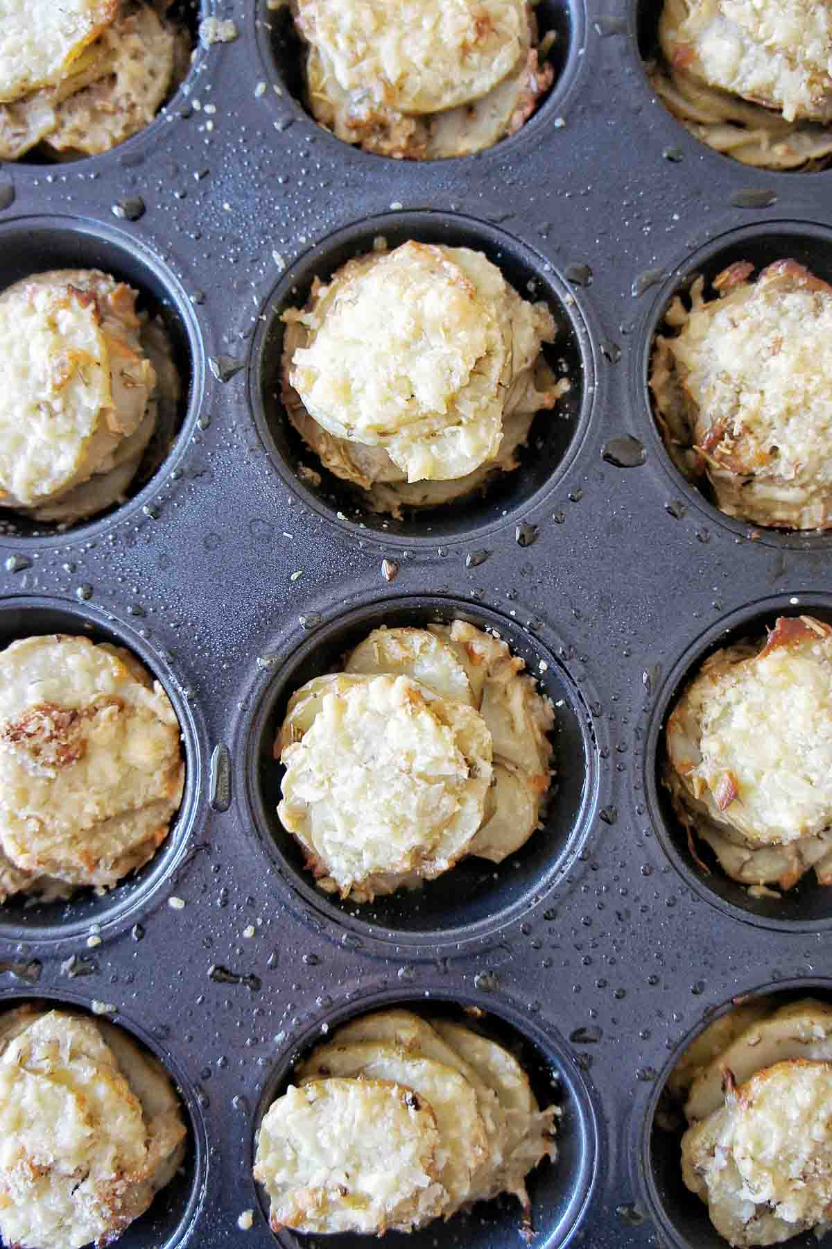 Potatoes stacked into muffin tin and topped with melted cheese