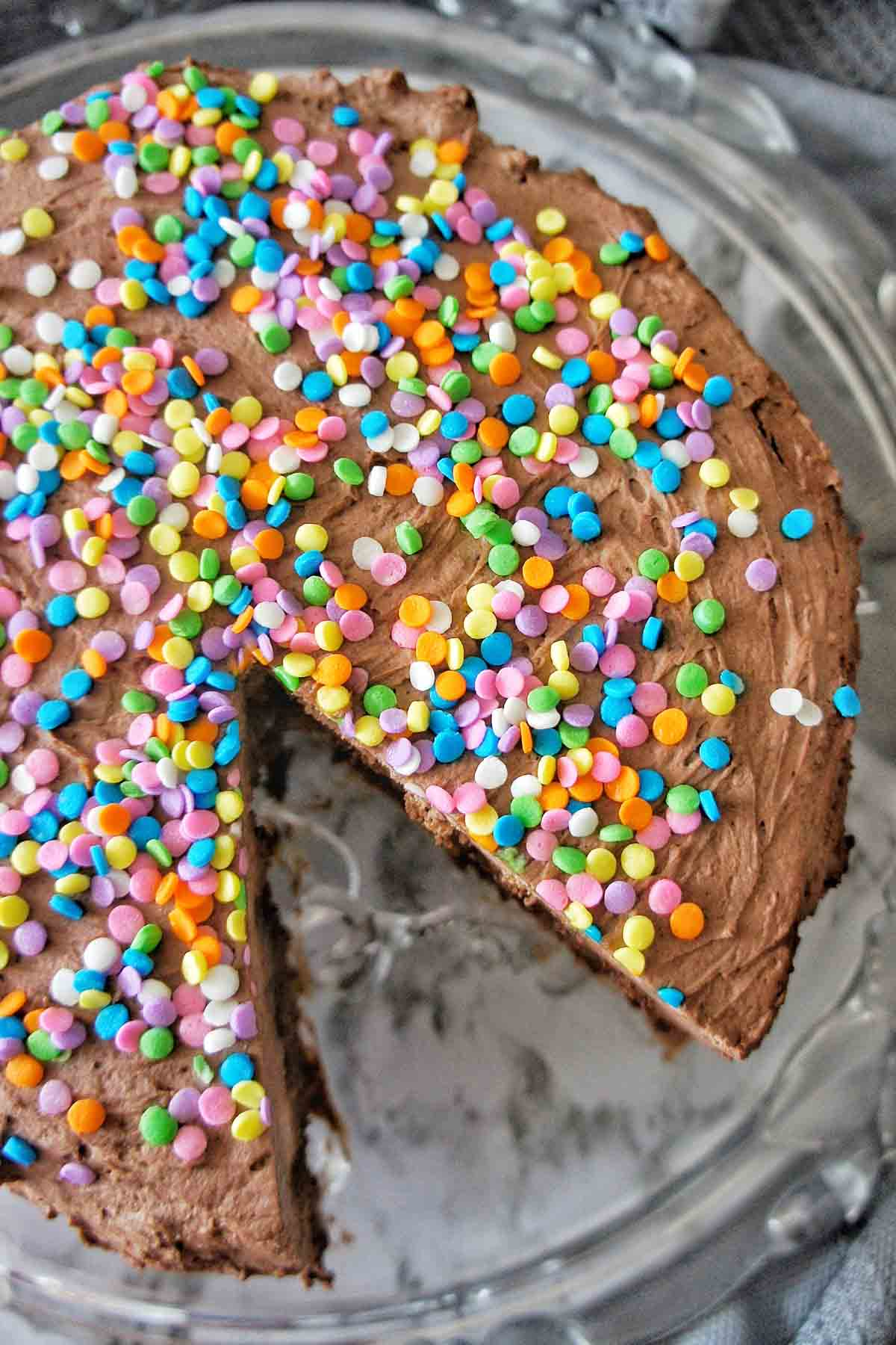 No Bake Chocolate Cake with slice cut out on a glass platter with chocolate cream and coloured sprinkles