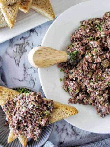 Olive Tapenade in a white bowl with some spread on toast points to the left