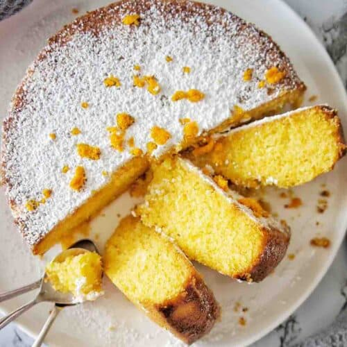 Orange Polenta Cake with cut slices on a white plate wither silver teaspooons