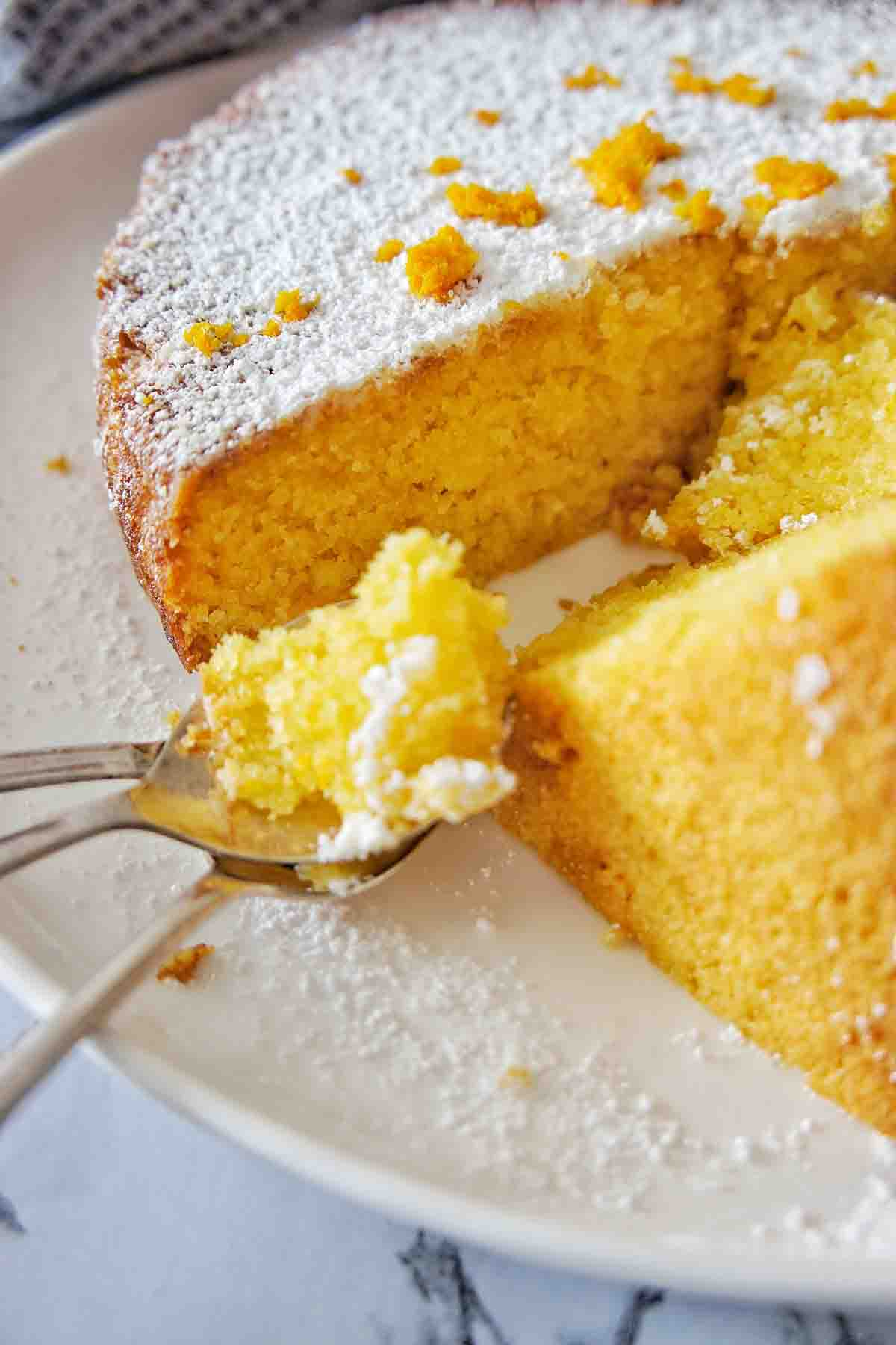 Orange Polenta Cake on a white plate with silver teaspoons