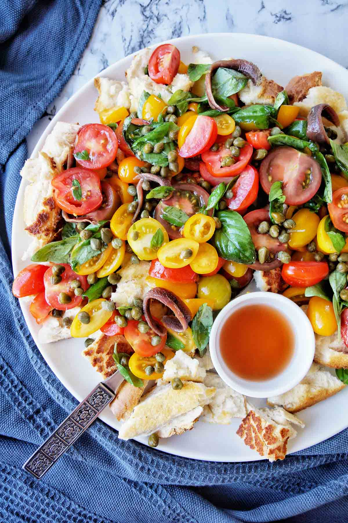 Panzanella Salad on a white plate with both of dressing