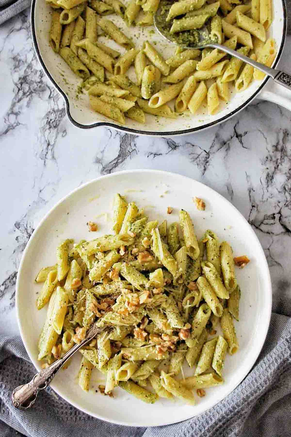Pesto penne on a plate with white skillet full of more pasta above