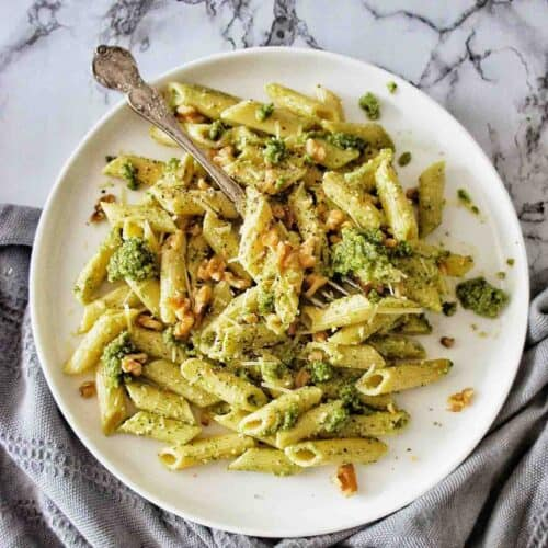 Pesto Penne on a white plate with a fork in the top left
