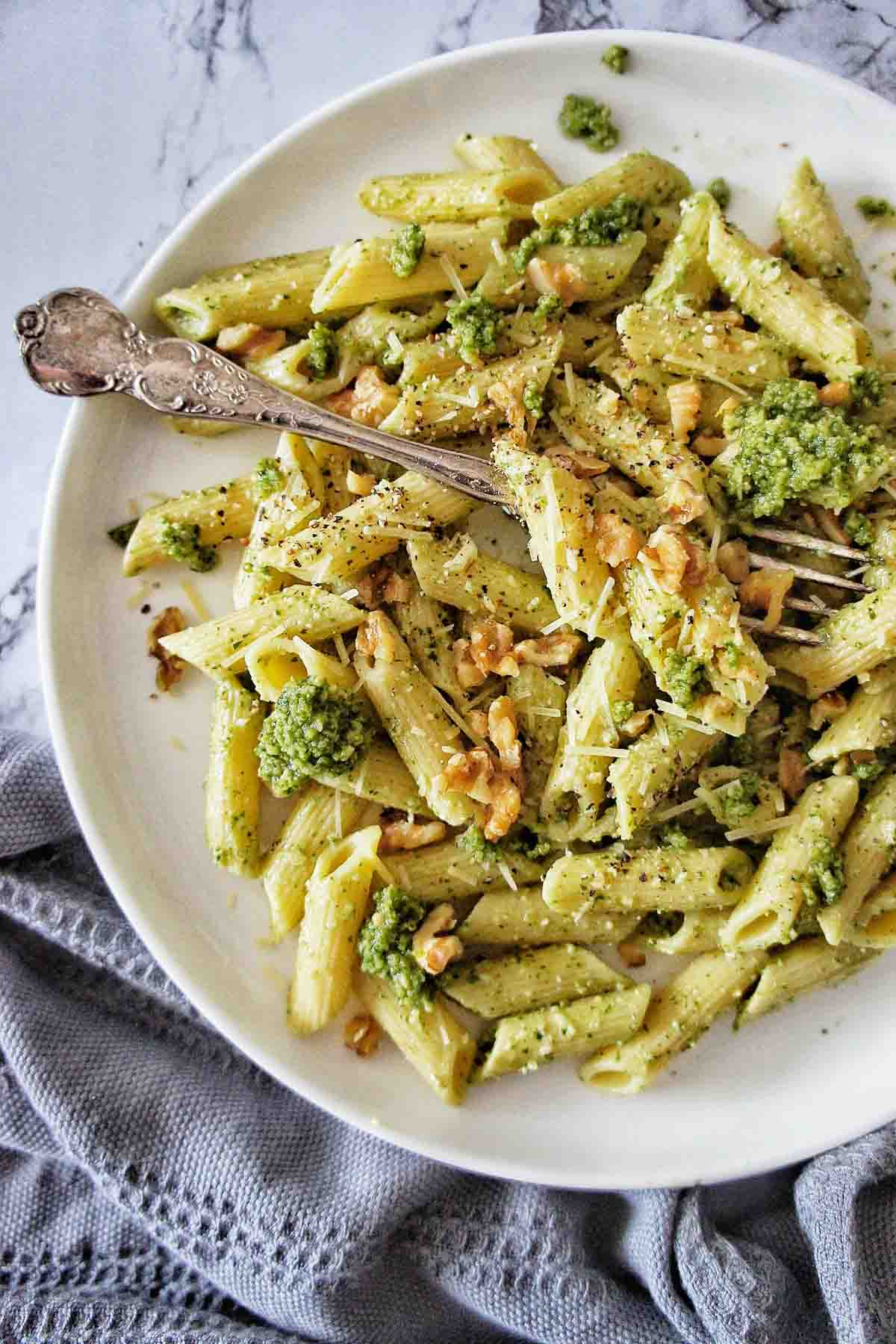 Pesto Penne on a white plate with walnut crumb on top