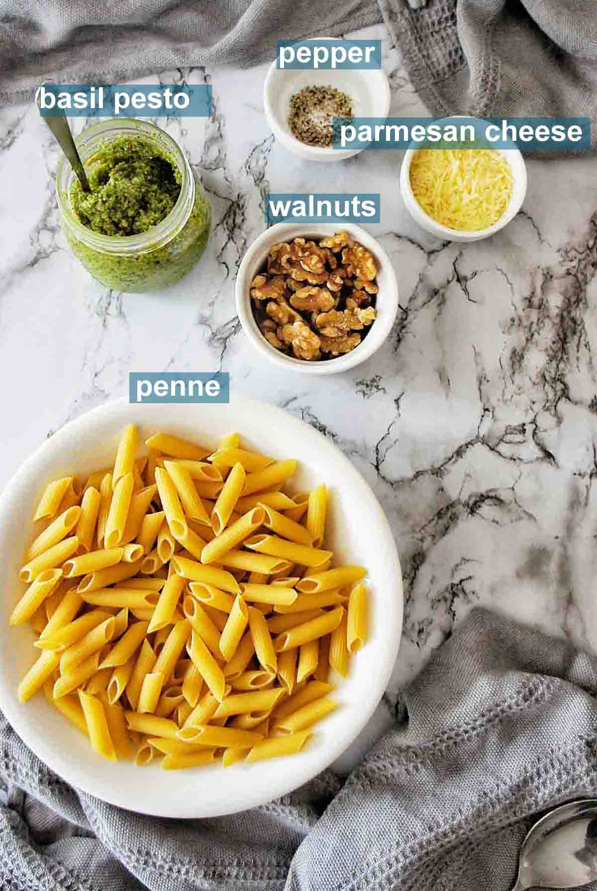 Pesto Penne ingredients on marble background with text over lay