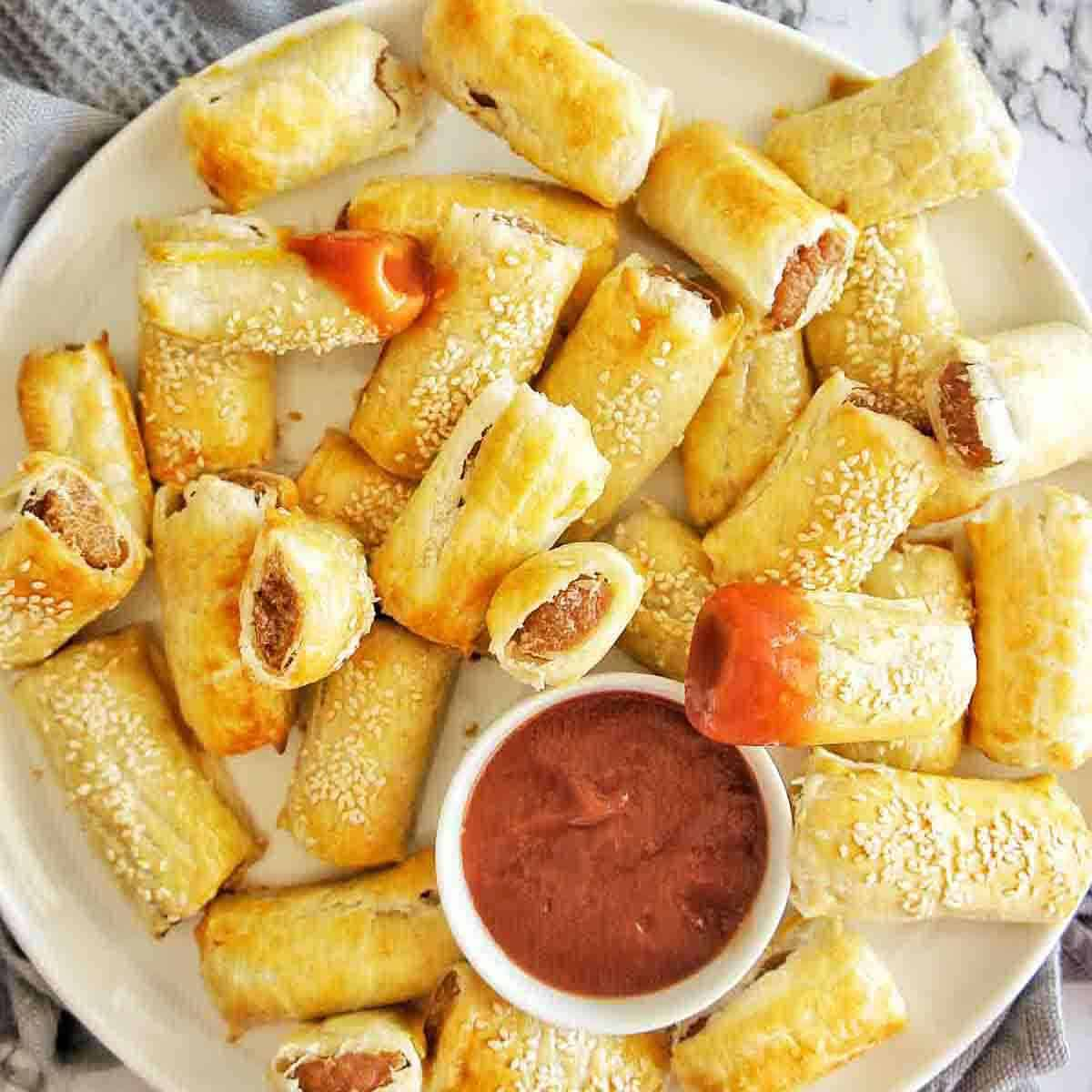 Sausage rolls on large white platter with bowl of tomato sauce