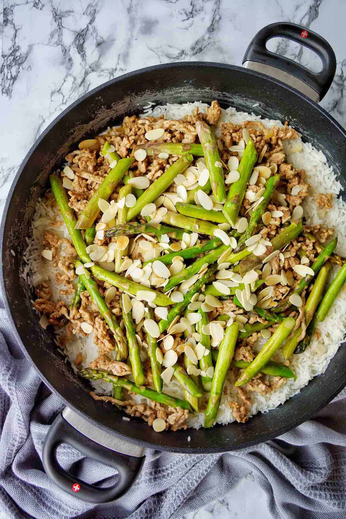 Asparagus and Pork in sauté pan with flaked almonds