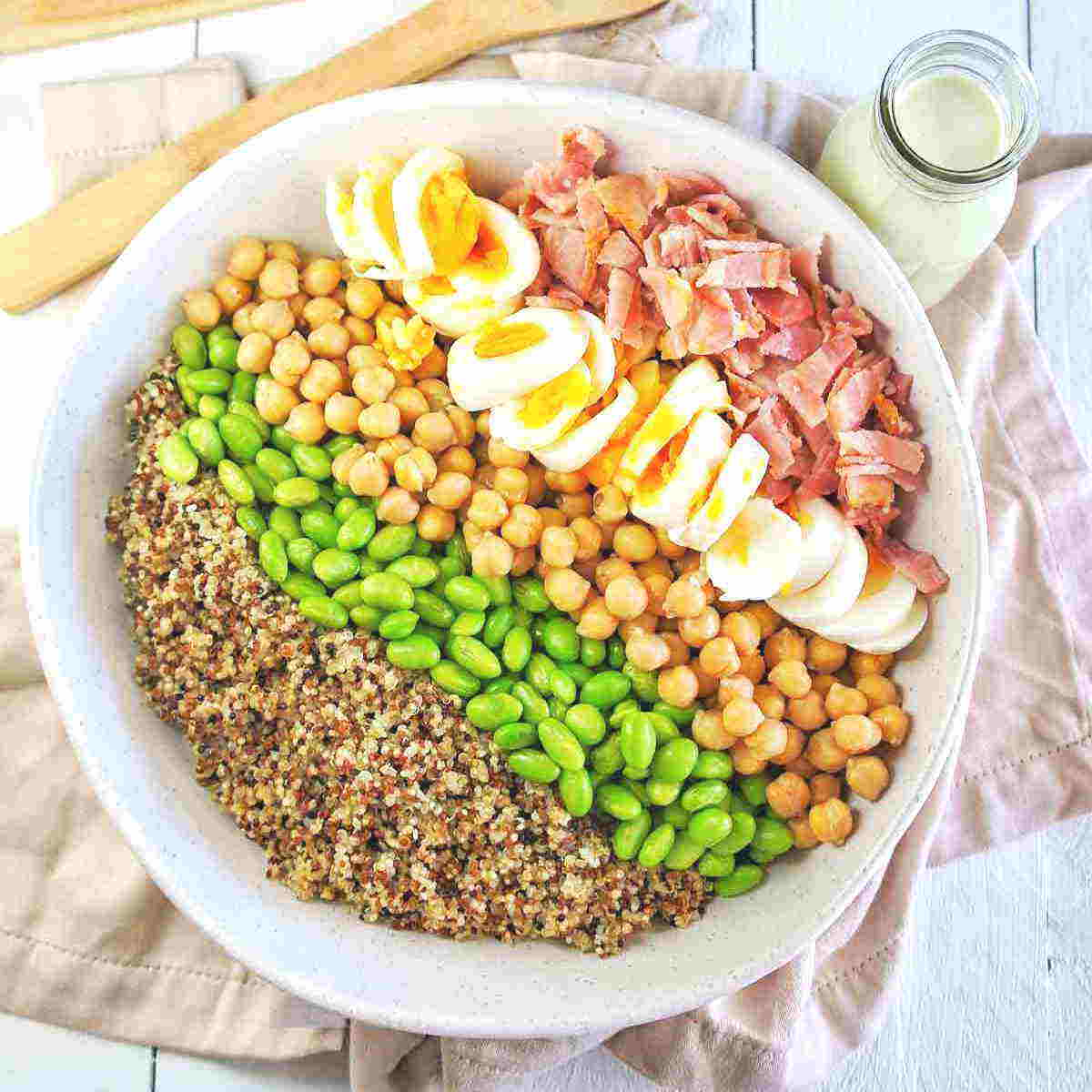 Edamame Quinoa Salad in a white bowl with dressing in the top right
