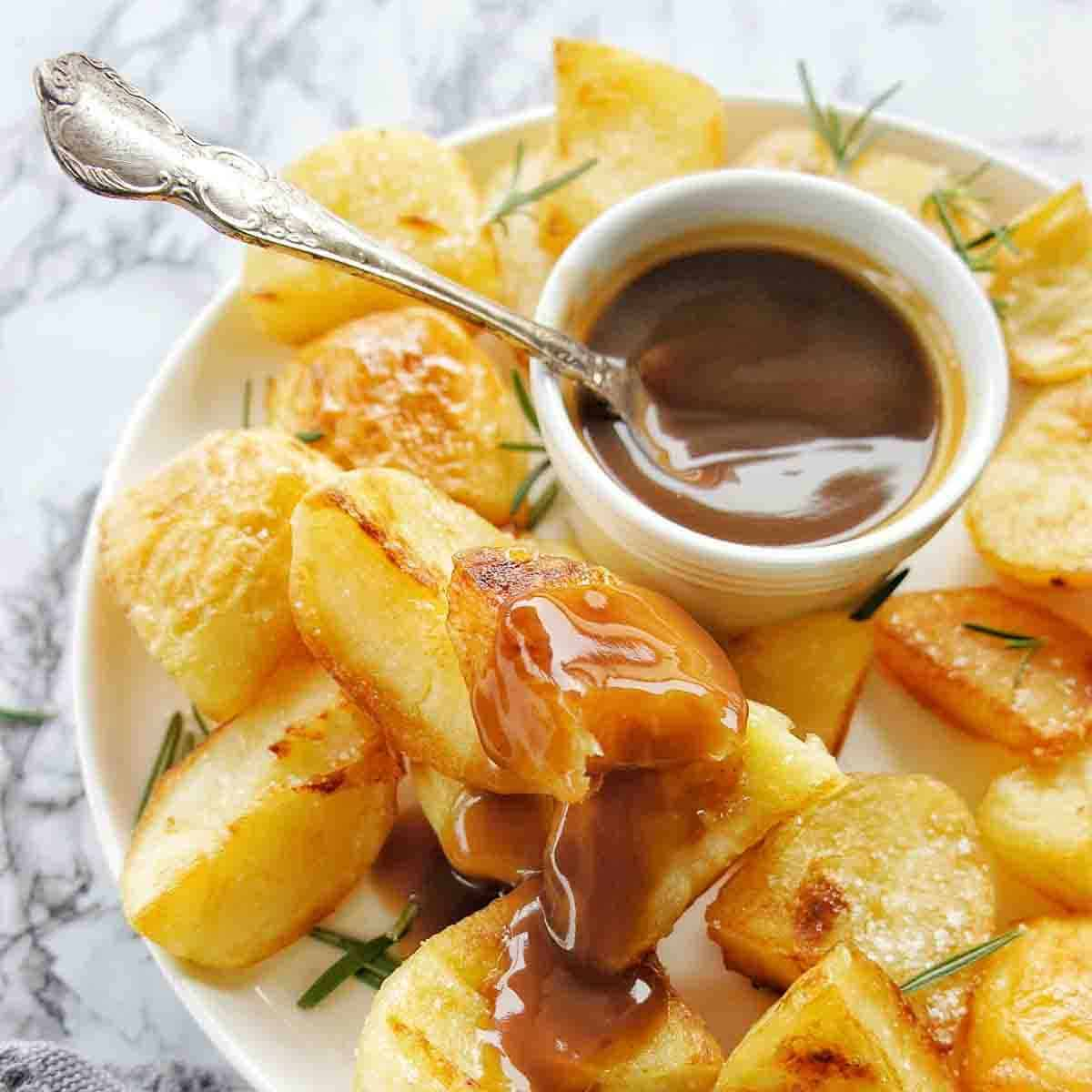 Roast Potatoes on a white plate with a small bowl of gravy