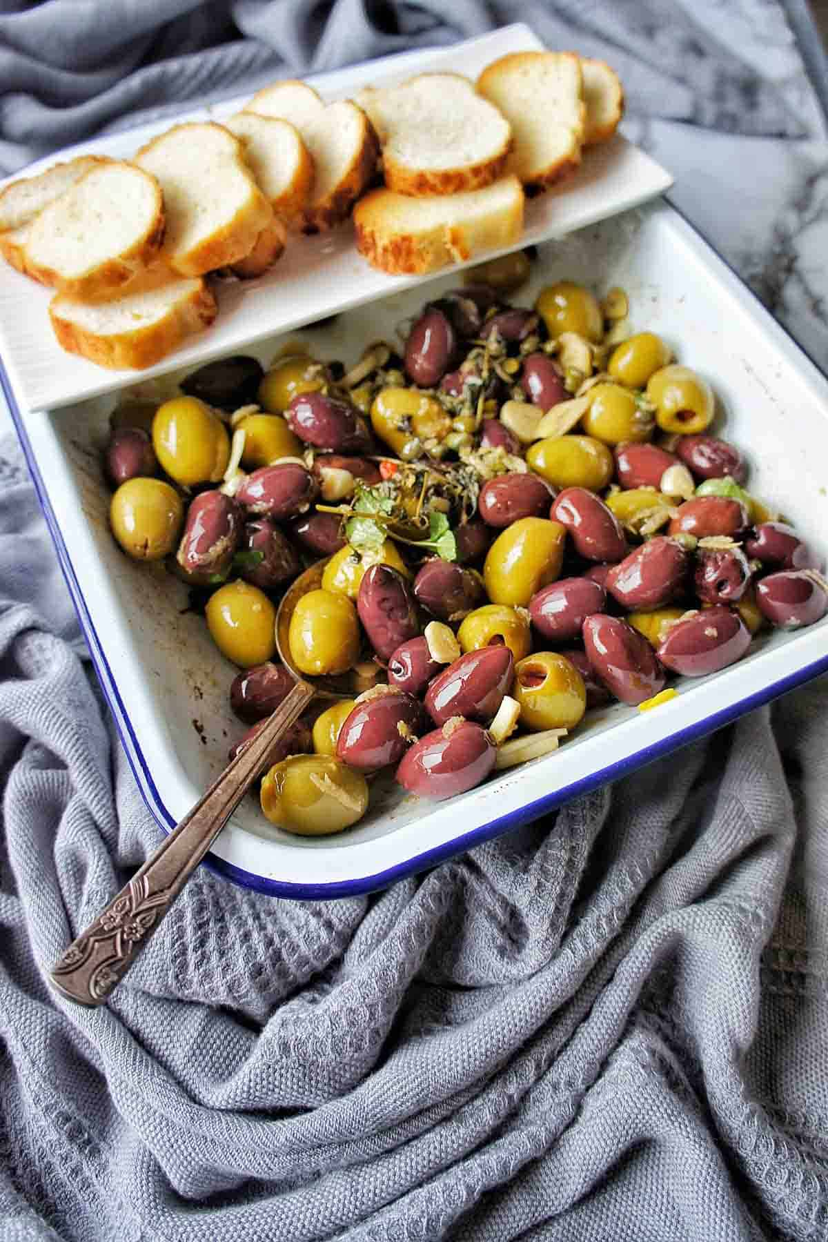 Roasted Olives in a white baking tray with mini toasts