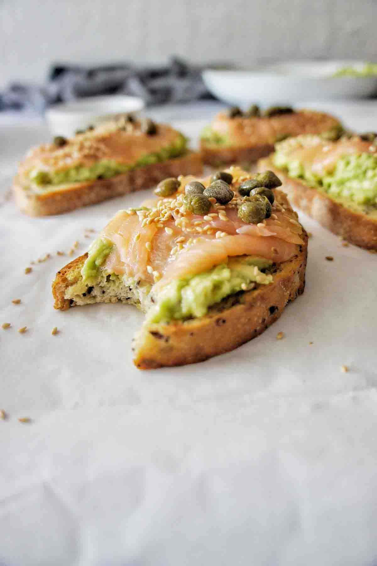Salmon Avocado Toast with a bite out of it on white background