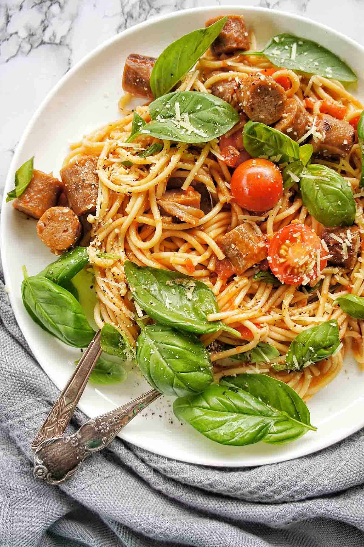 Sausage Spaghetti on a white plate with grey napkin