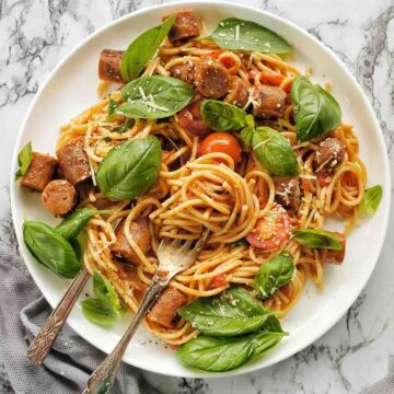 Sausage Spaghetti on a white plate with spoon and fork down to the left