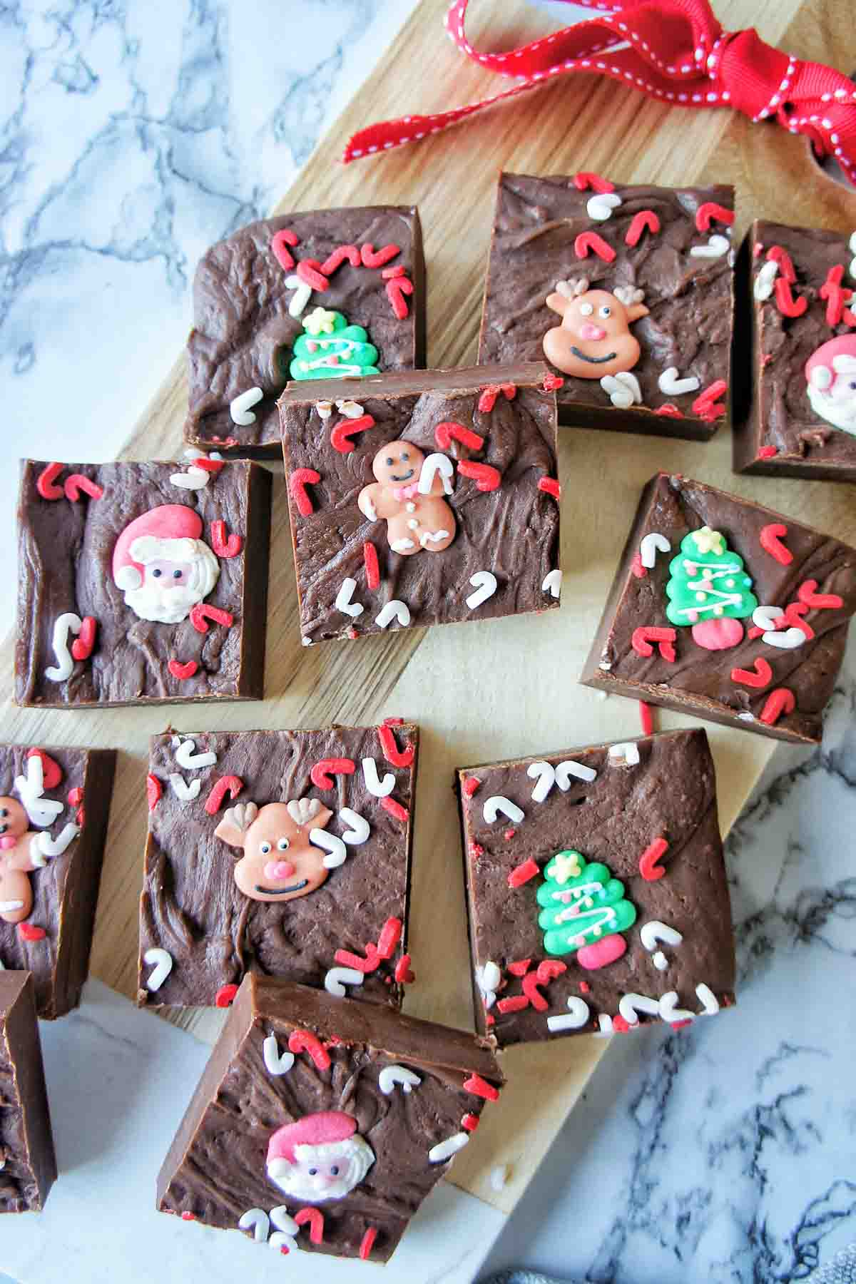Pieces of fudge with Christmas sprinkles on a chopping board