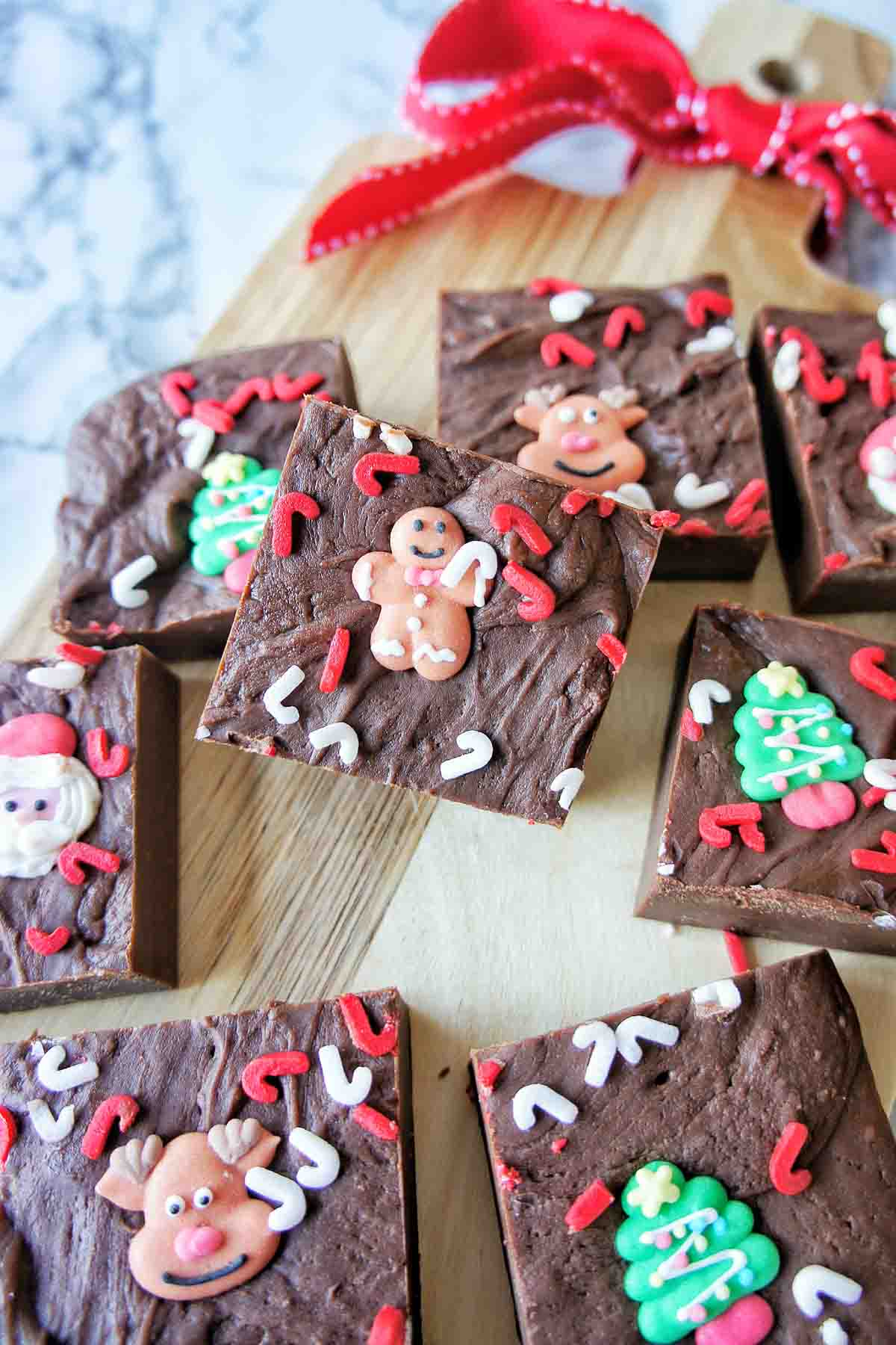 Slow Cooker Christmas Fudge cut into pieces on a chopping board with red ribbon in the background