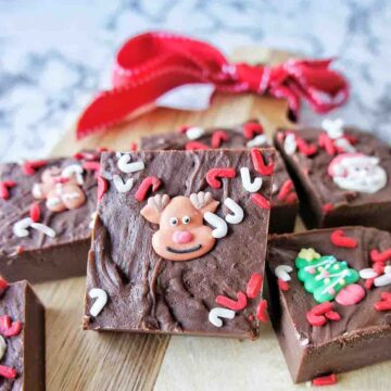 Pieces of chocolate fudge with Christmas sprinkles on a timber chopping board
