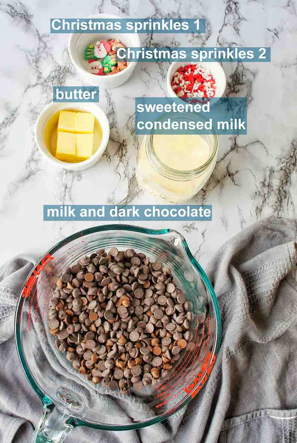 Slow Cooker Christmas Fudge ingredients on marble background with text labels