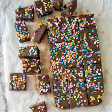 Slow Cooker Fudge with multi coloured sprinkles on a white baking sheet