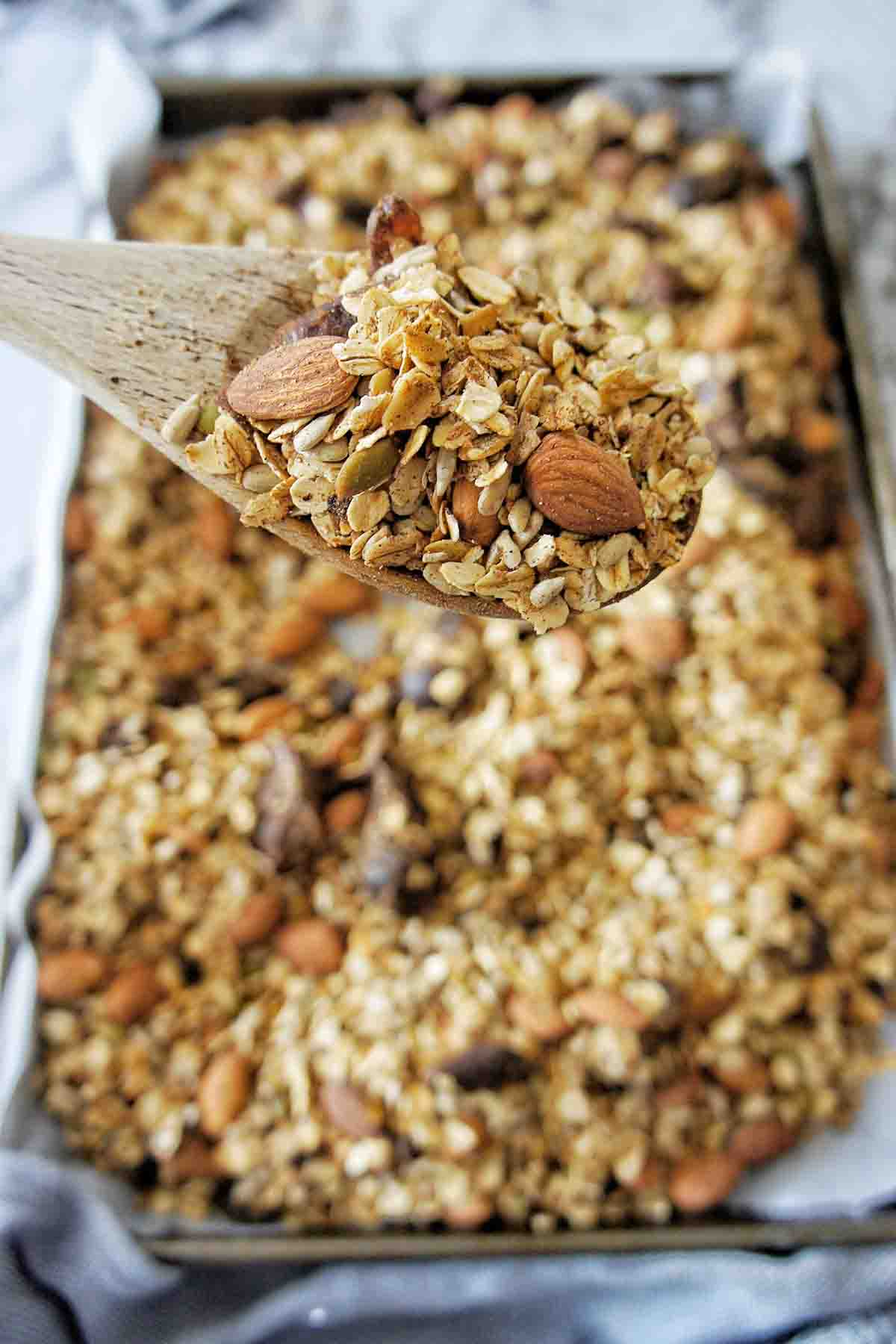Spoon of slow cooked granola above a baking tray of the same