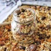 Slow Cooker Granola in glass jar surrounded by more granola and a spoon