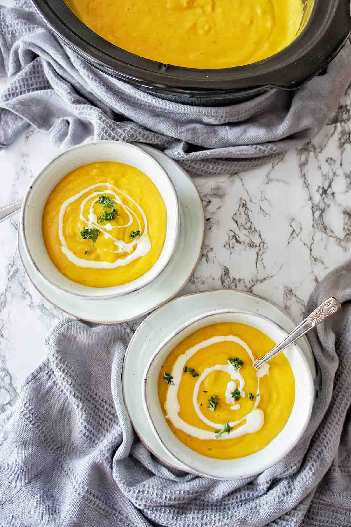 Pumpkin soup in 2 blue bowls with crock pot in the background