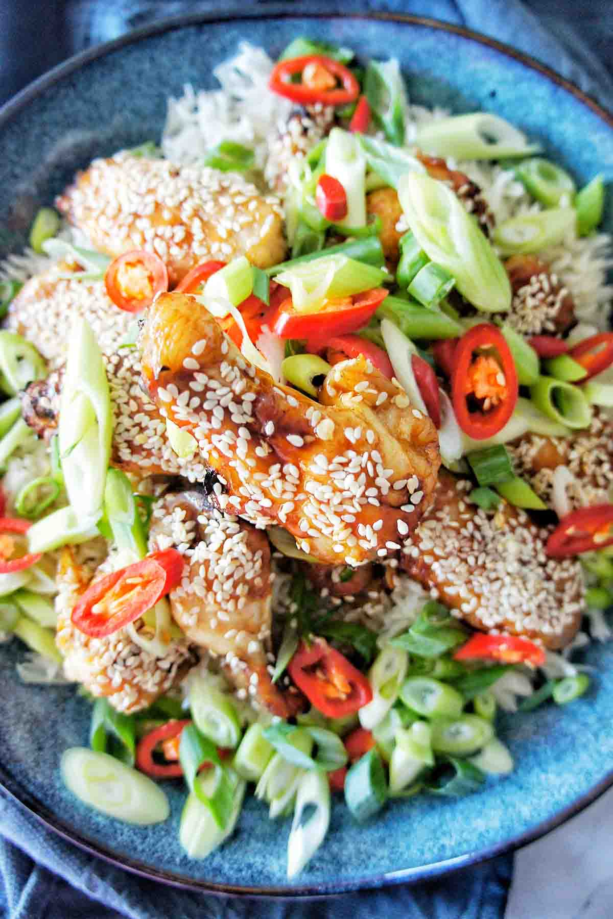 Sticky Chicken wings in a blue bowl with white rice, green sliced onions, red chilli and sesame seeds