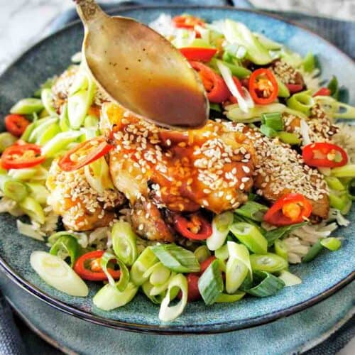 Spoon pouring sauce over bowl of chicken wings that have sliced shallots, red chilli and sesame seeds on them