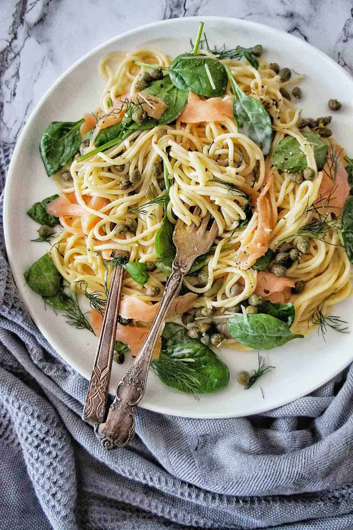 Smoked Salmon Spaghetti on a white plate with spoon and fork