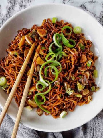 Soy Sauce noodles in a white bowl with scallions on top