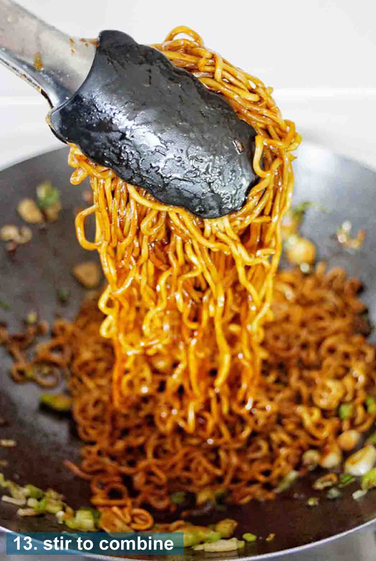 Tongs holding noodles above a wok of the same