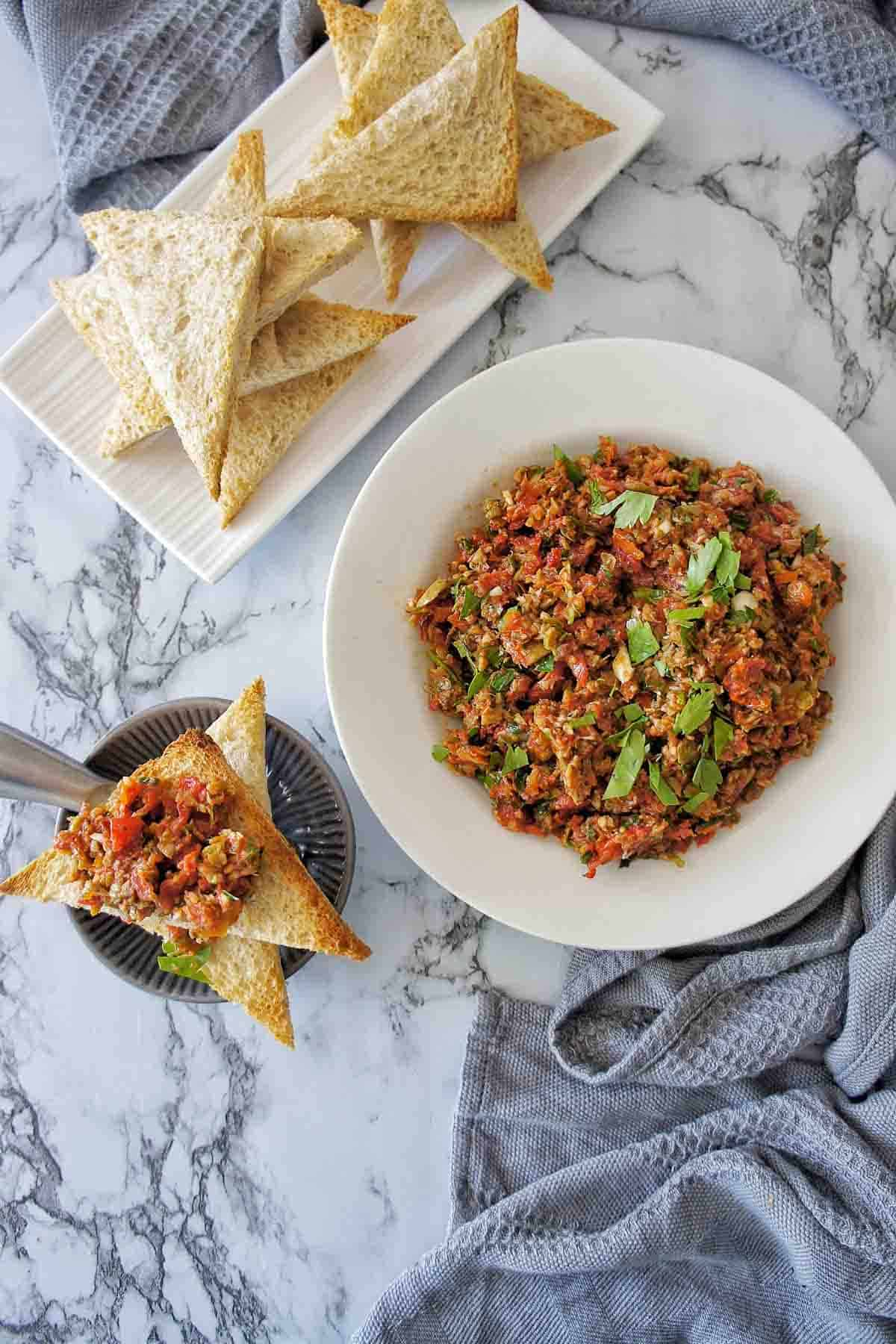 Sun-dried tomato tapenade in a white bowl with toast points to the side and above