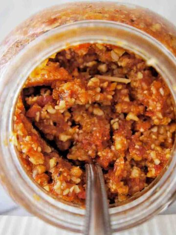 Sundried Tomato Pesto in a jar on its side with a spoon coming out