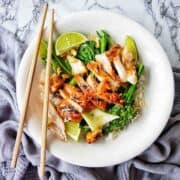 Sweet Chilli Chicken Thighs in a white bowl with greens and rice