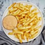 Sweet Chilli Mayo in a small bowl on plate of cooked fries