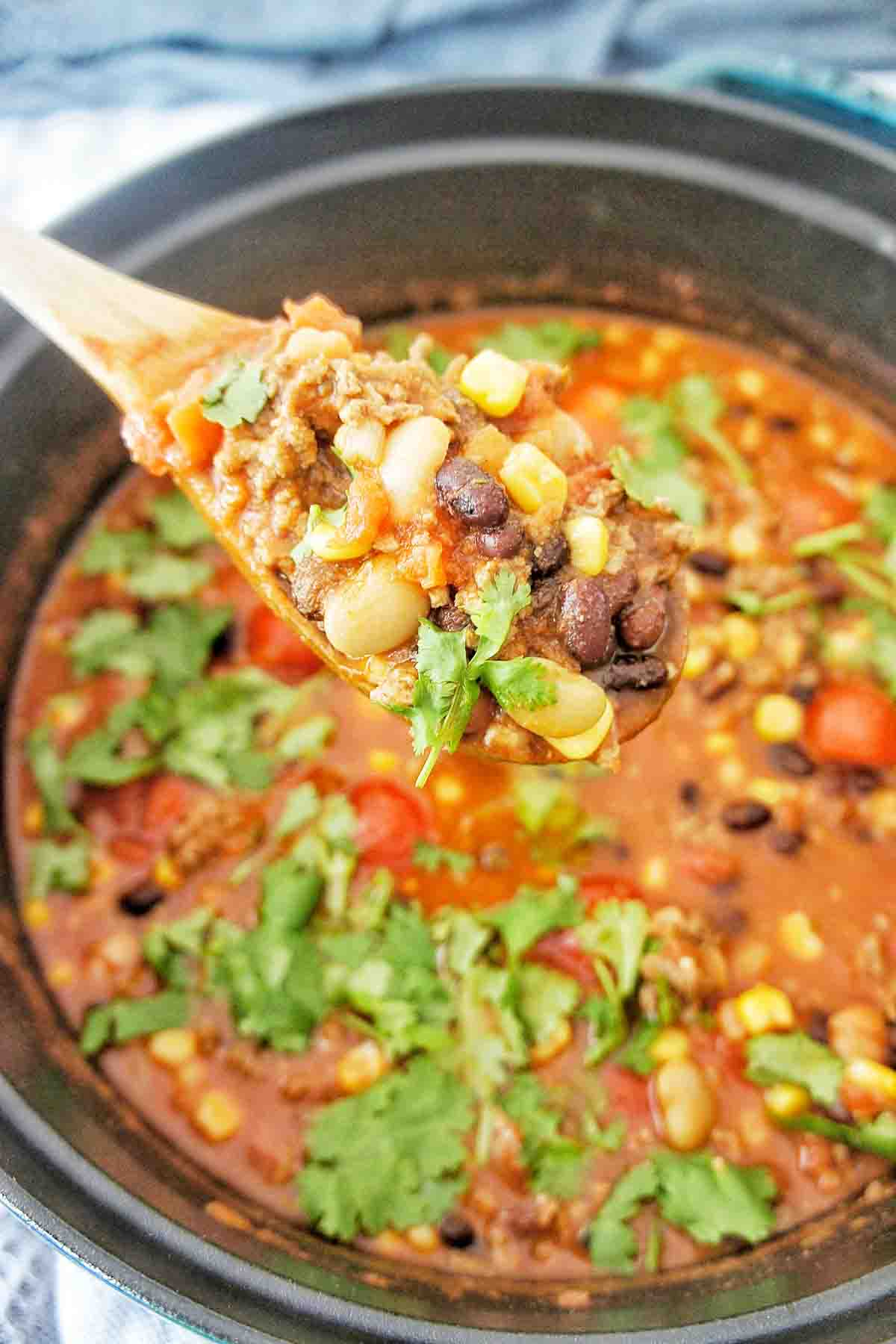 Spoon holding taco soup above a cast iron pot
