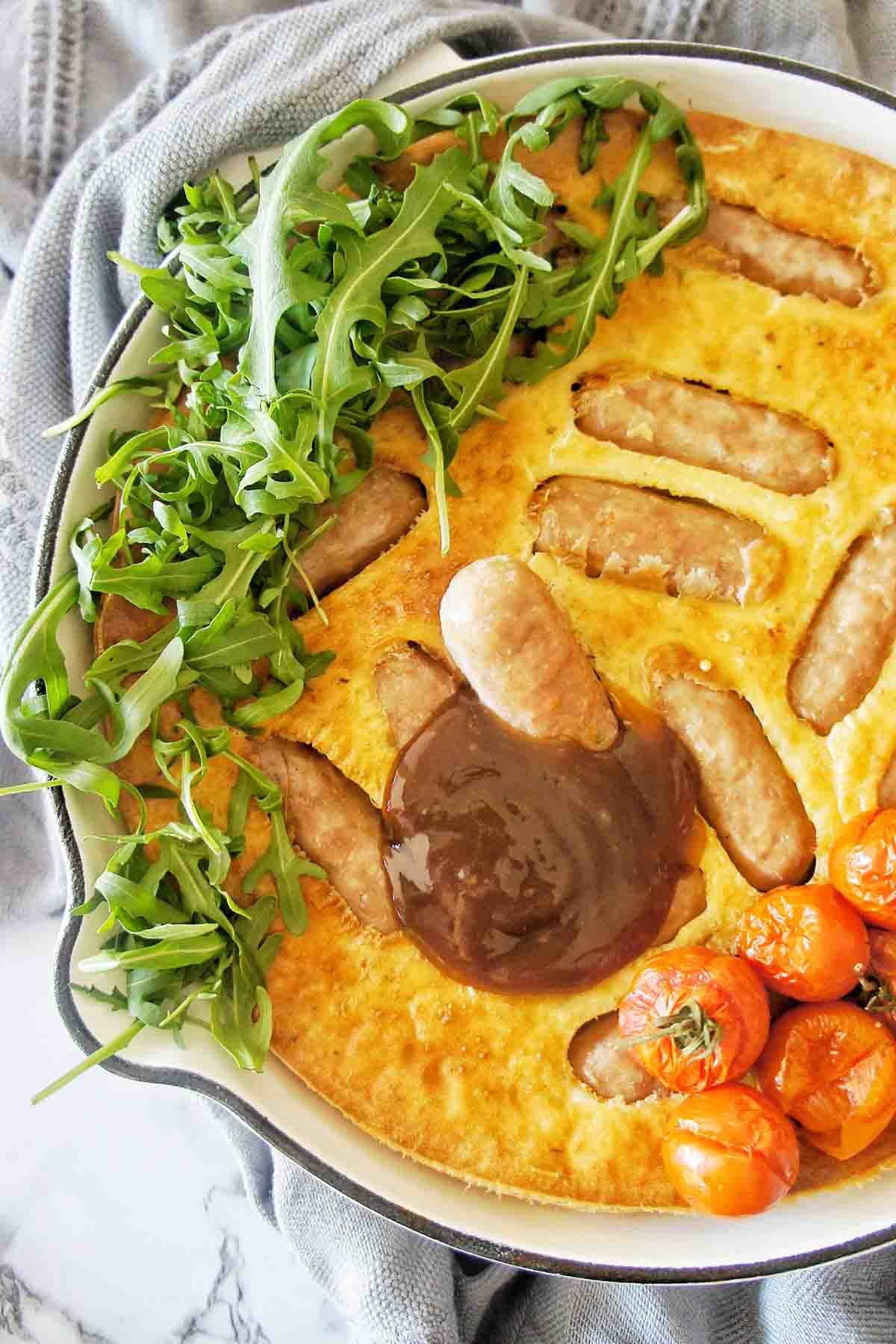Pork Chipolata in pool of gravy pudding in a white skillet