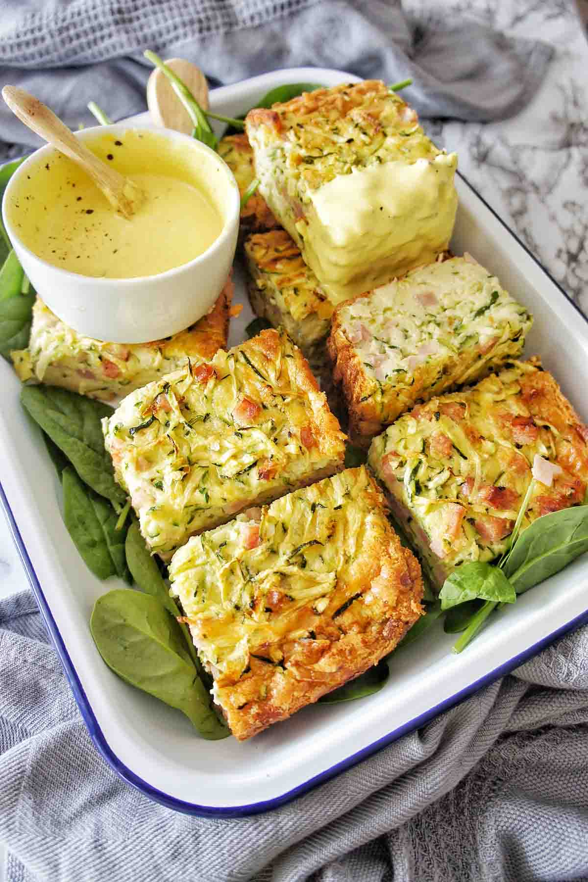 Zucchini Slice cut into pieces in a white tray with yellow sauce