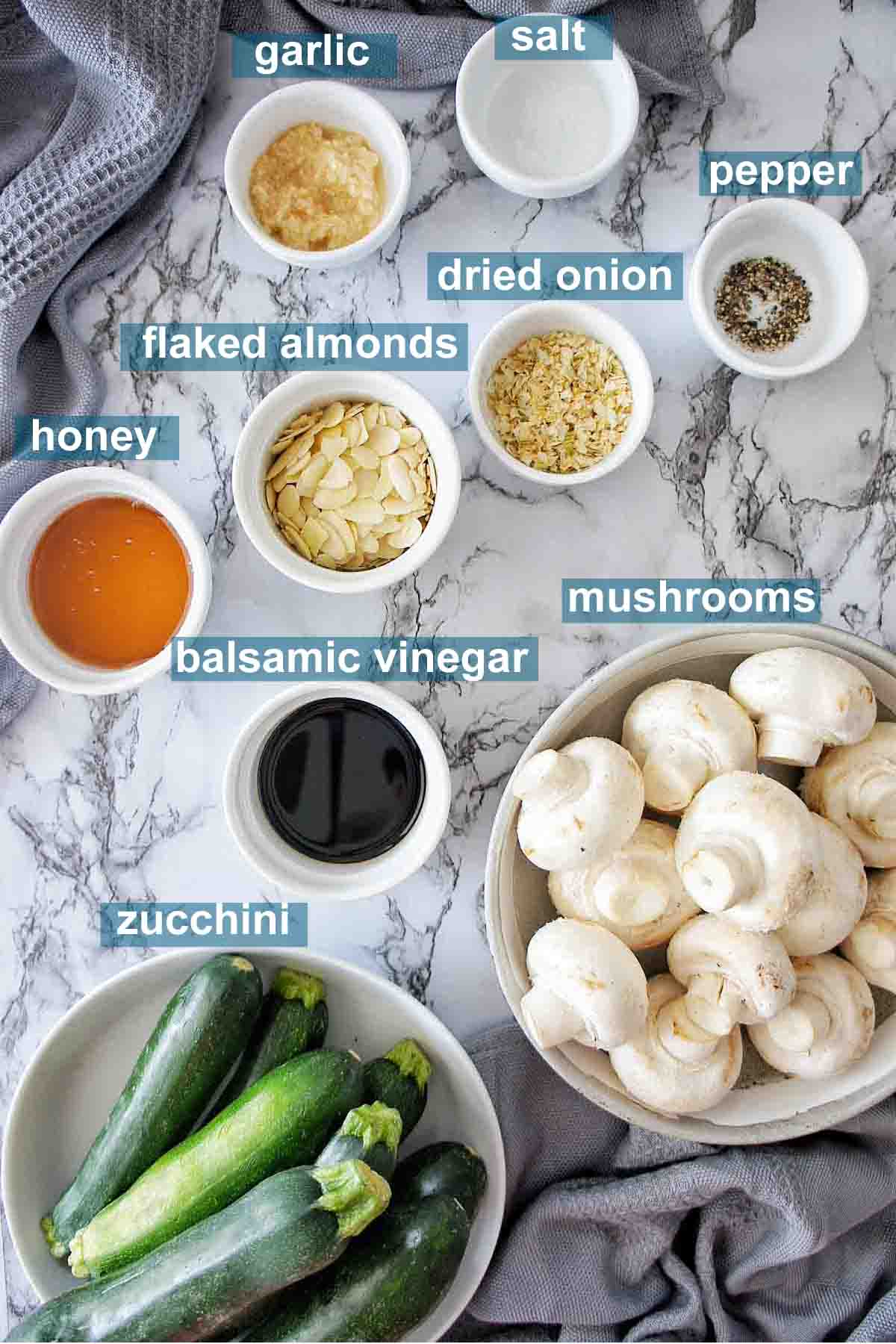 Ingredients for sauteed zucchini and mushrooms on a marble background with text overlay